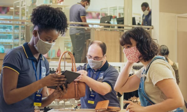 Dois funcionários da Pernambucanas atendendo cliente na loja, os três usam máscara