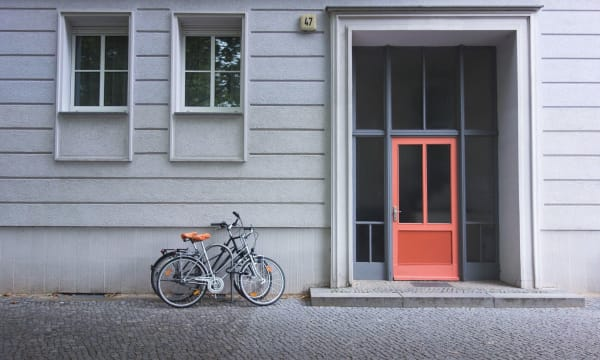 front entrance of house with red door and two bicycles