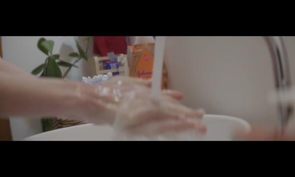 Pessoa com a torneira aberta lavando as mãos, sabonete liquido Johnson & Johnson no fundo