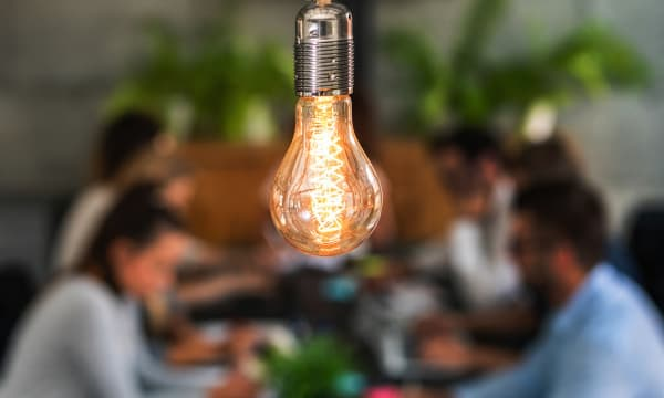 group of people at the table with light bulb