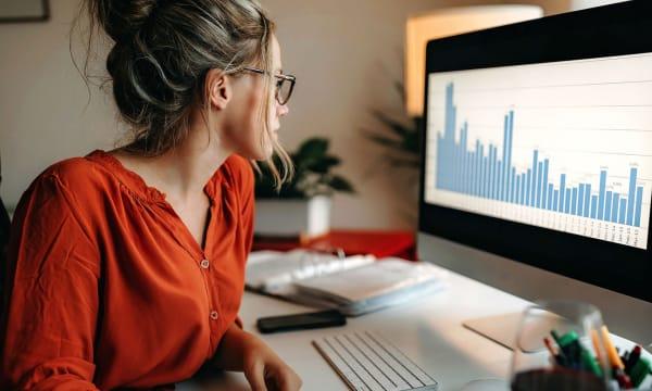 woman looking at graph on monitor