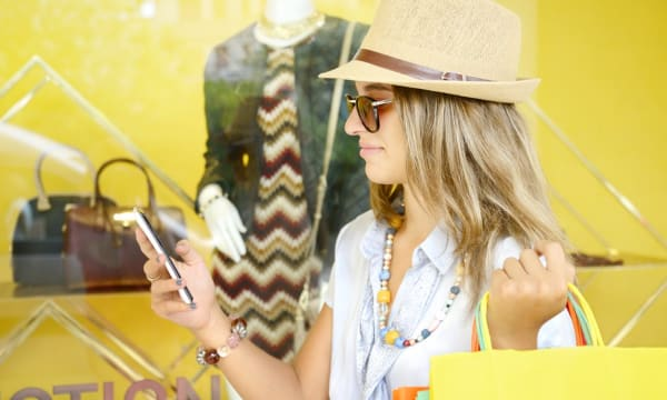 Woman looking at phone while shopping