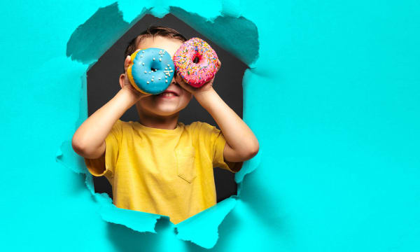 Child with donuts covering eyes