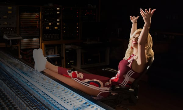 Blonde woman in maroon track suit, leaning back in chair with her arms up. Feet up against sounds panel in a recording studio