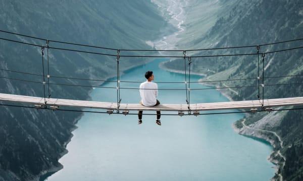 Man sitting on bridge over river
