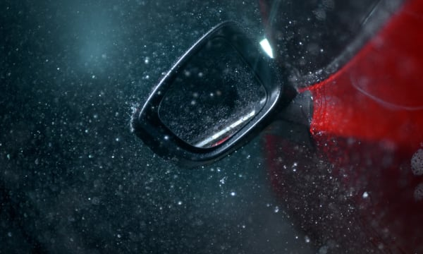 Black background with night scene of rain coming down over red Mazda door and the drivers side mirror.