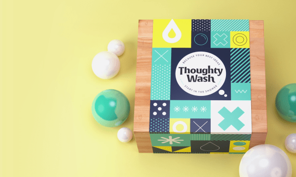 Yellow background. A square wooden box with a wrap around saying Thoughty Wash. Green and white baubles surround the box.