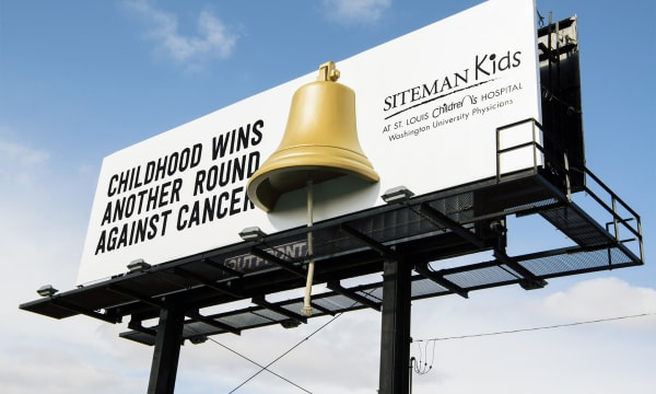 Blue sky, with a billboard in the for front with a 3-D bell. Childhood wins another round against cancer.