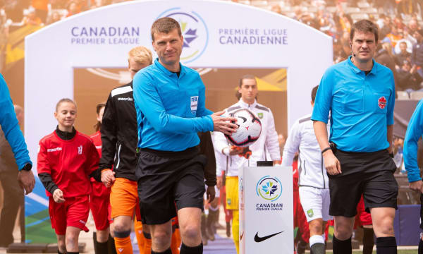 Referee in blue shirt holding the soccer ball. Players behind him and a archway saying CPL