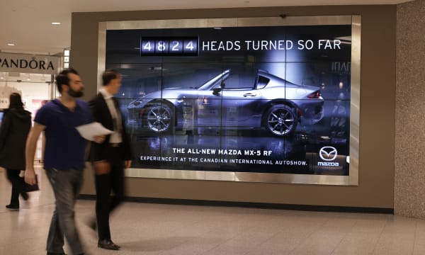 Underground mall, people walking past a Mazda billboard saying # of heads turned so far.