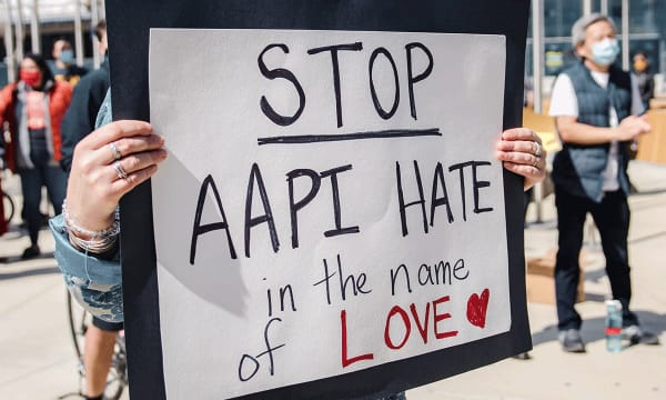 person holding a sign that reads Stop AAPI Hate