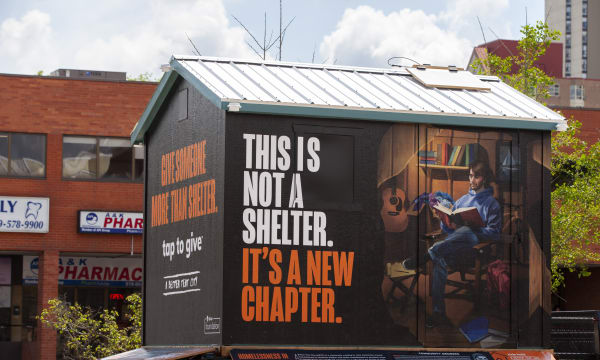 """small house elevated with the words printed: """"This is not a shelter. It's a new chapter."""""""