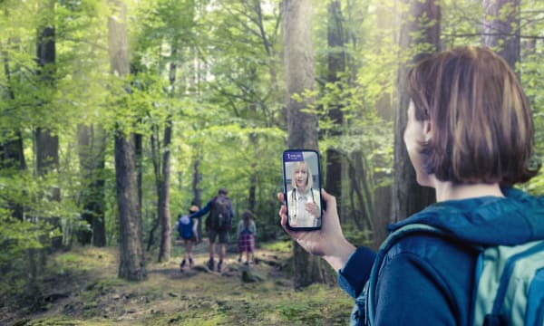 brown haired women holding smartphone walking in the forest