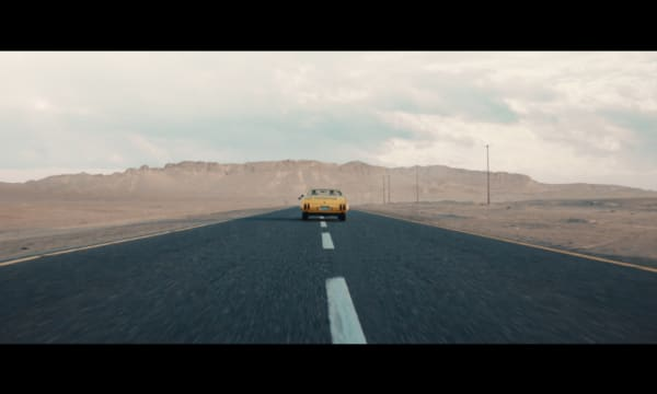 A still from Ahli United Bank's Al-Hassad TVC, which shows a seventies American muscle car driving in the middle an empty road, of what looks to be the Nevada desert