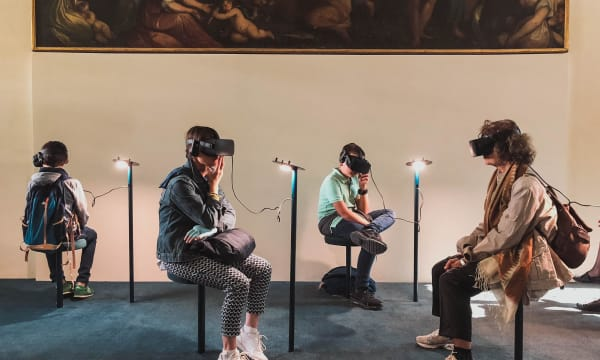 four people in a museum seated and following a 3D demo