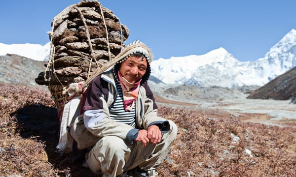 Sherpa with backpack in the mountains
