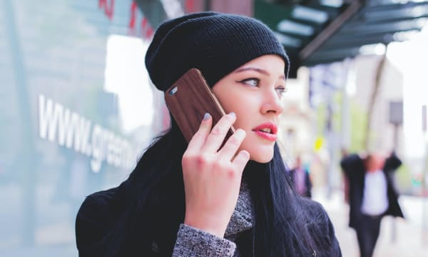 Woman in beanie hat on mobile phone