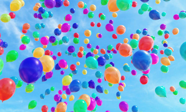Multiple multi-coloured balloons released in the sky