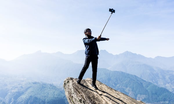 person taking a selfie at a rock overhang