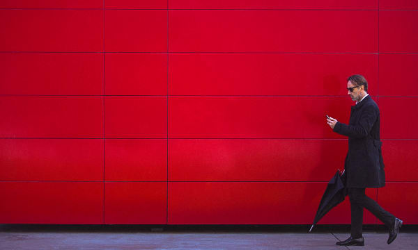 business man in front of red coloured wall