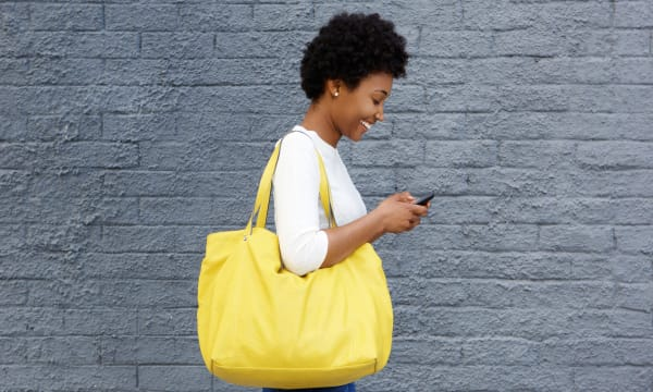 Smiling woman with iPhone and big yellow bag