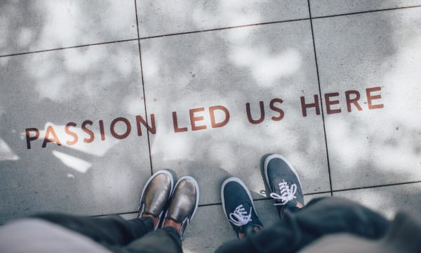two people looking at a floor paining that reads: Passion led us here