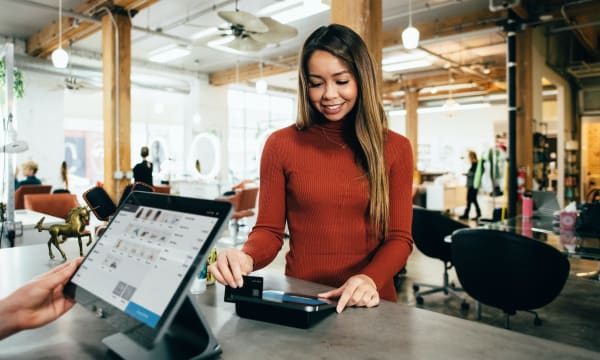 Girl at checkout paying by credit card