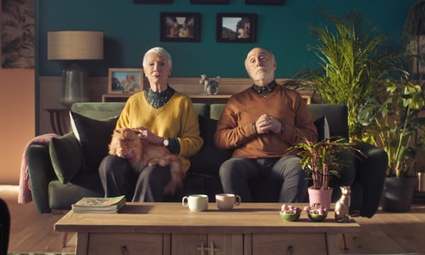 elderly couple sitting on couch in their living room