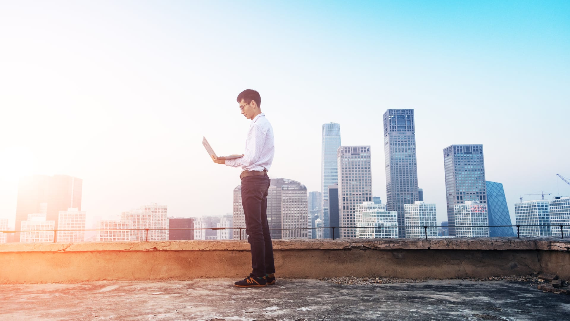 Man standing on a city roof with laptop