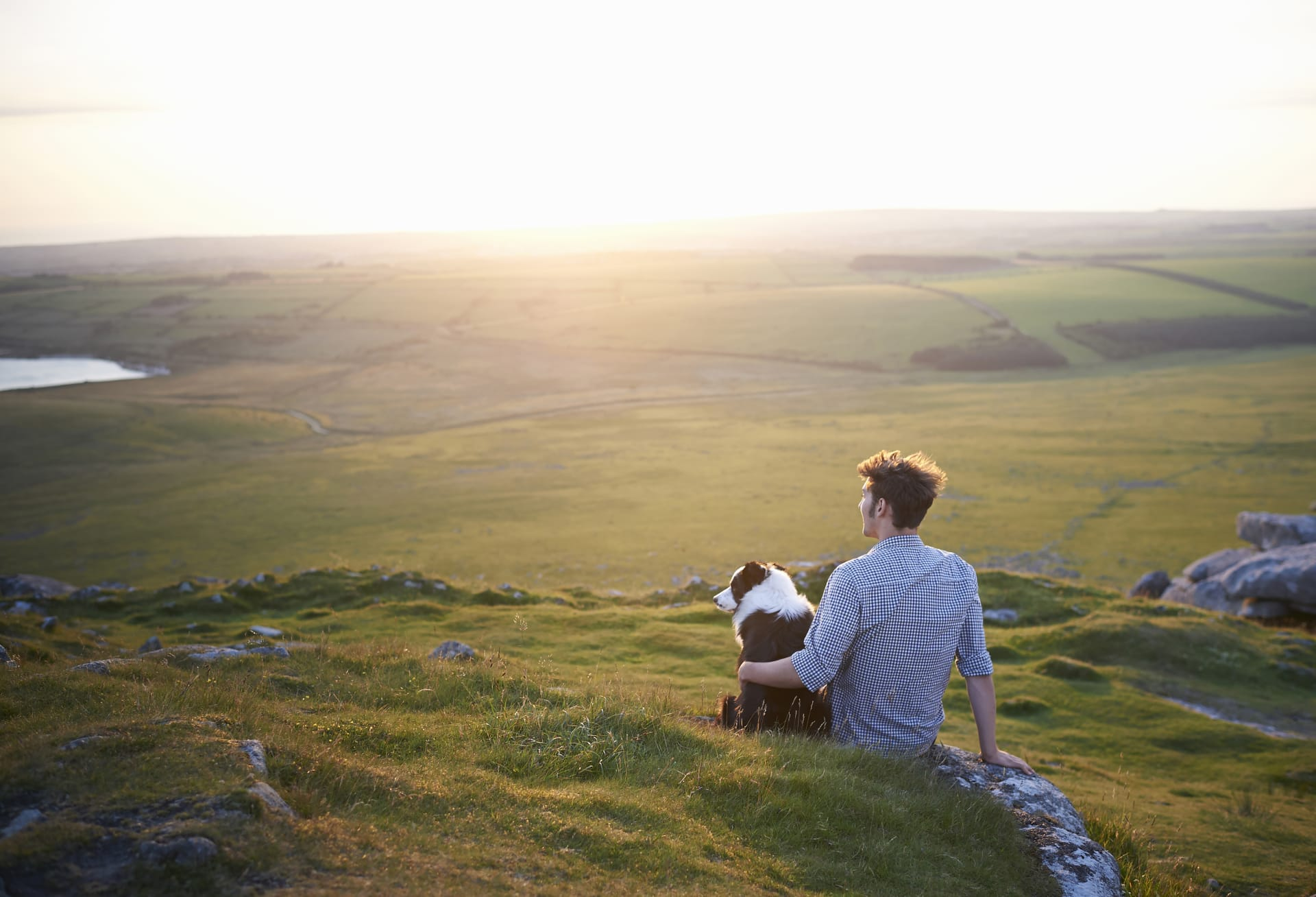 person with dog sitting on the ground in screen landscape
