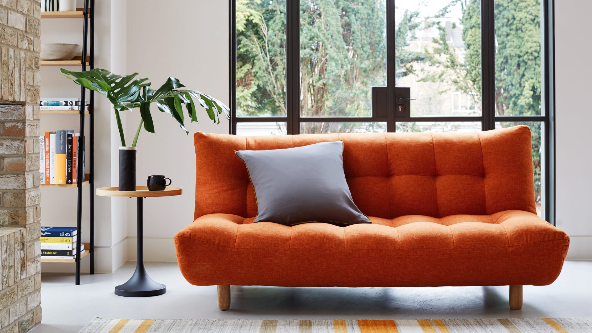 orange sofa in front of window in living room
