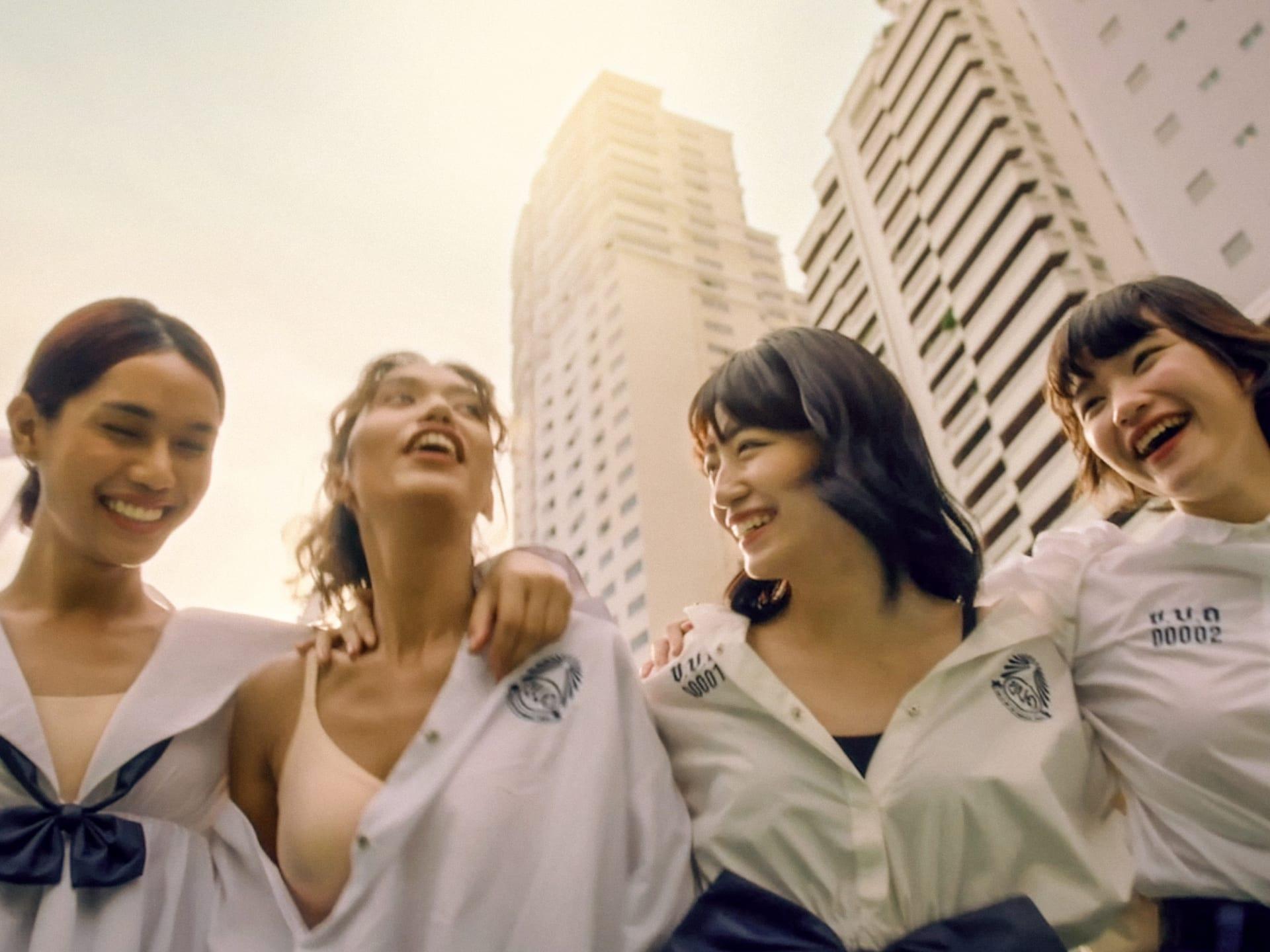 four women in front of a skyscraper skyline
