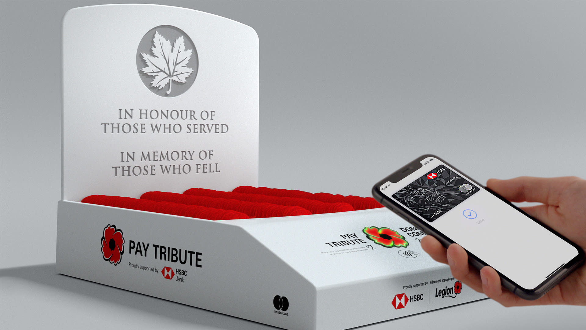 """White background, Pay Tribute box containing poppies. Hand in front holding cellphone with the HSBC RCL Pay Tribute App. Words on the box """"In honour of those who served. In memory of those who fell."""