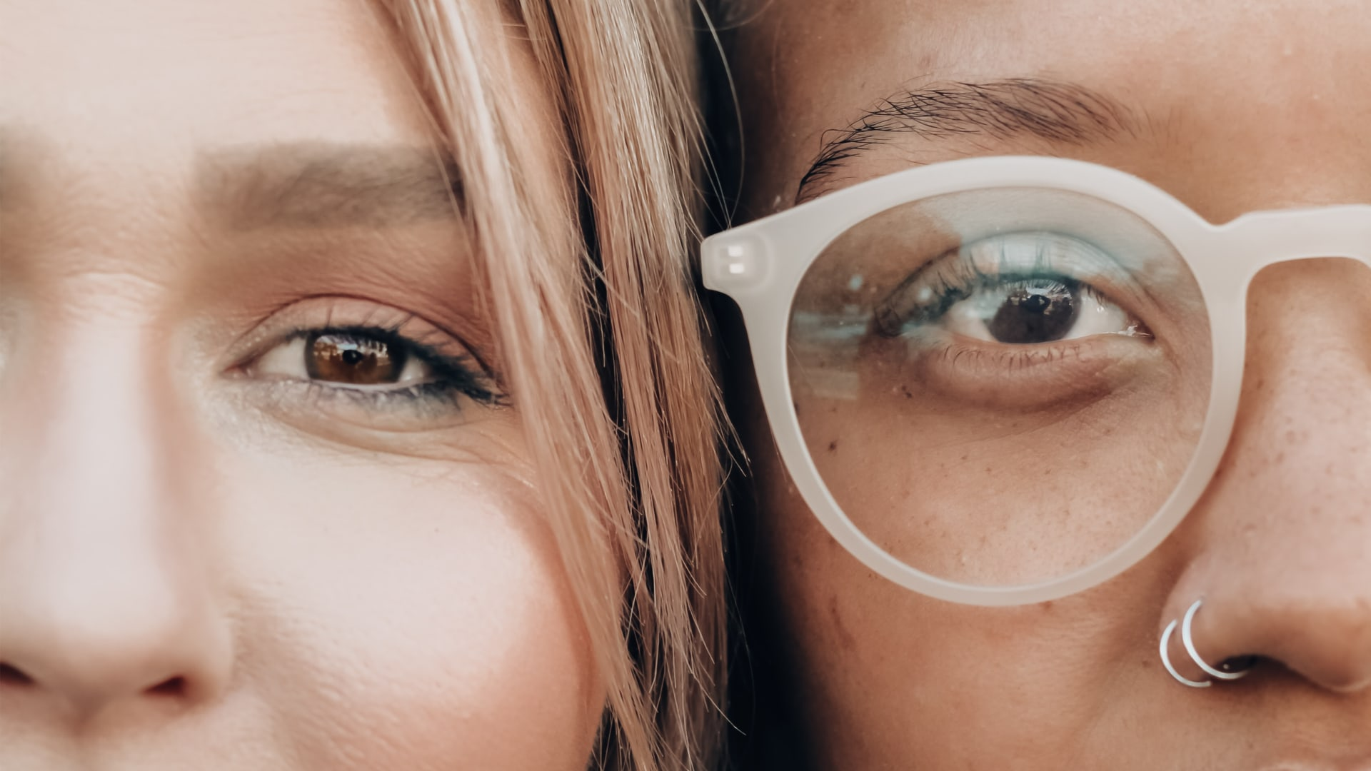 two female faces one with one without glasses