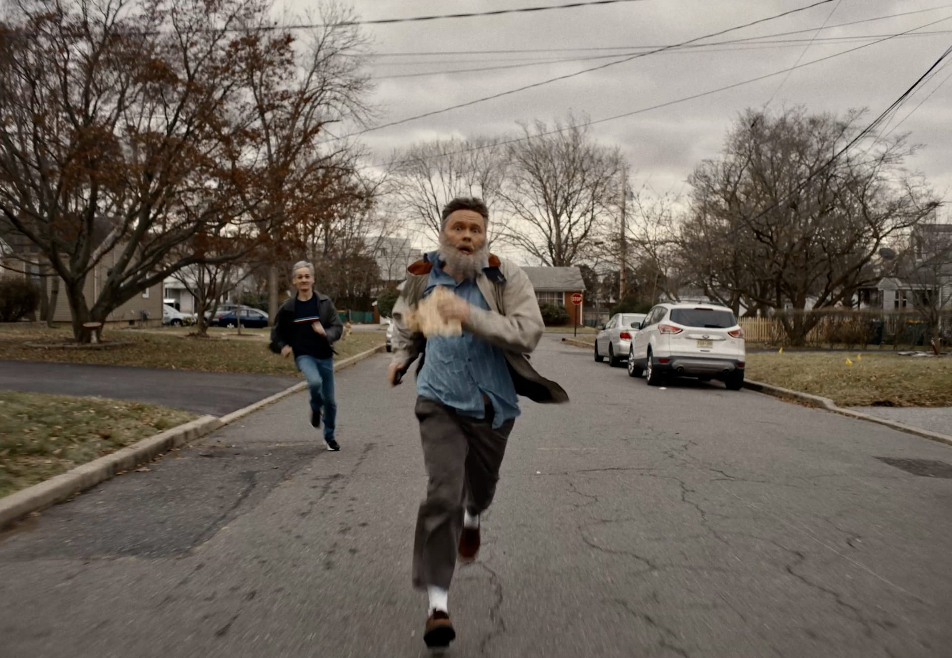 man running in the streets followed by another person running behind