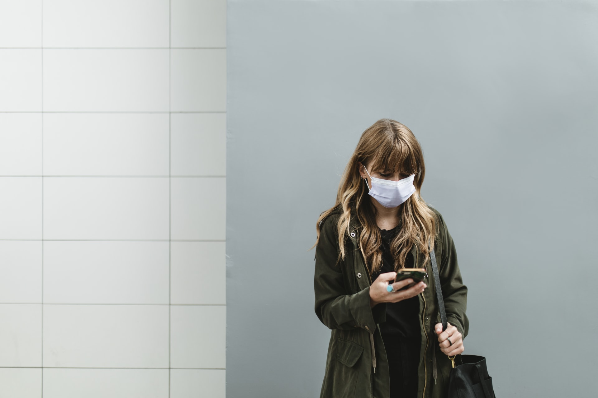 woman wearing a mask looking at her mobile phone