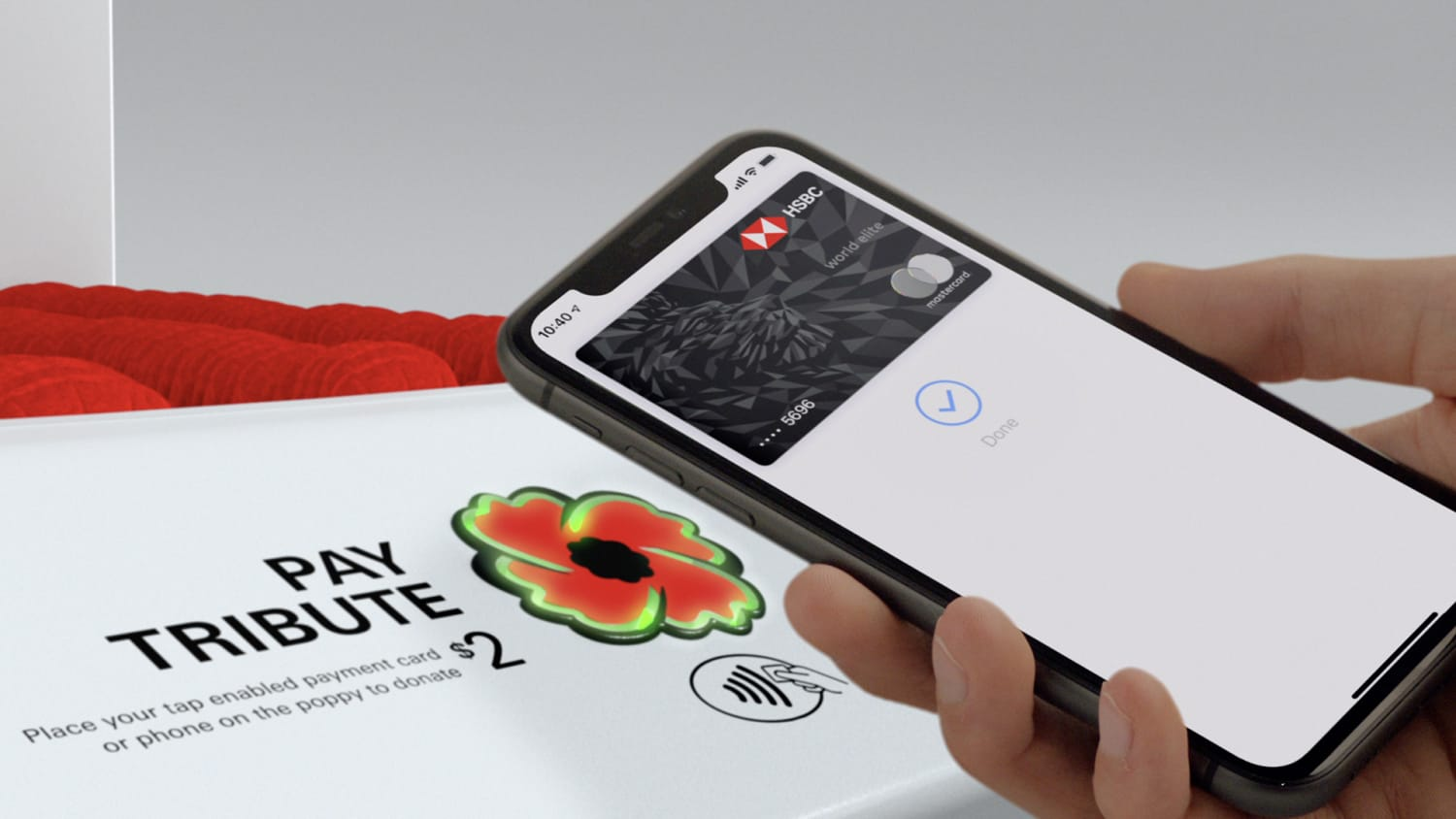 Close up of White background, Pay Tribute box containing poppies. Hand in front holding cellphone with the HSBC RCL Pay Tribute