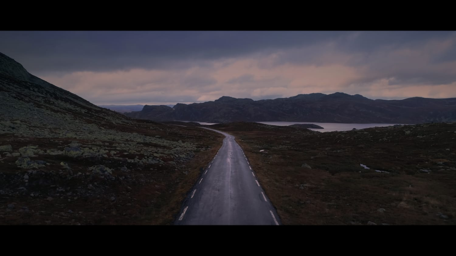 Shot of a empty winding road through mountains and lake, sunrise.