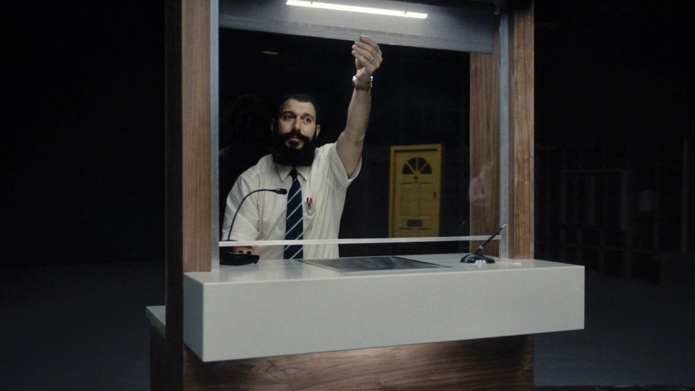 Man behind glass imitating a bank cashier
