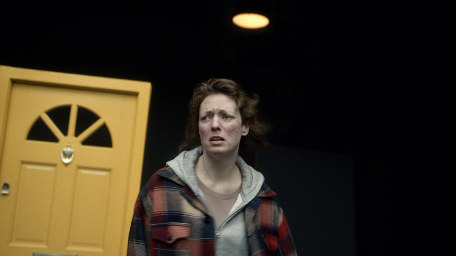 Woman in distress in front of a yellow door
