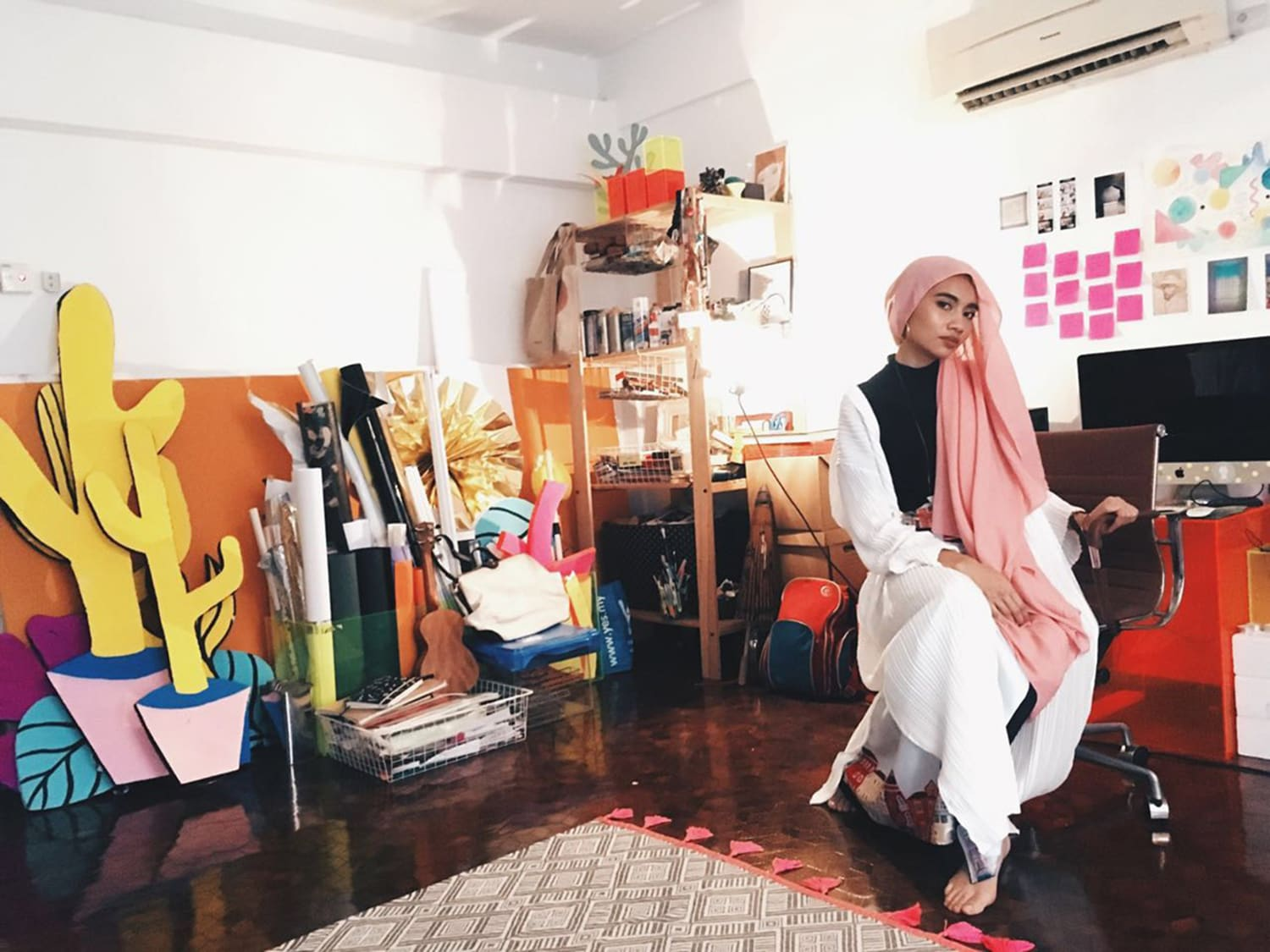 Malaysian pop singer songwriter Yuna sitting on a chair in her fashion studio