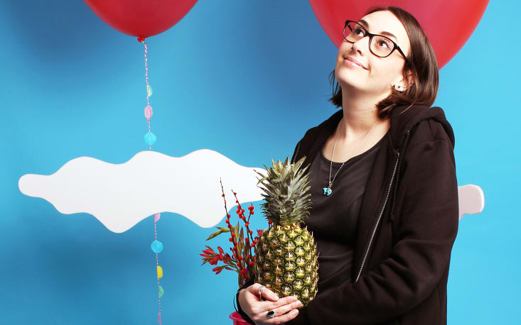 Woman in back tracksuit jacket holding a pineapple. Red balloons and clouds in back ground.