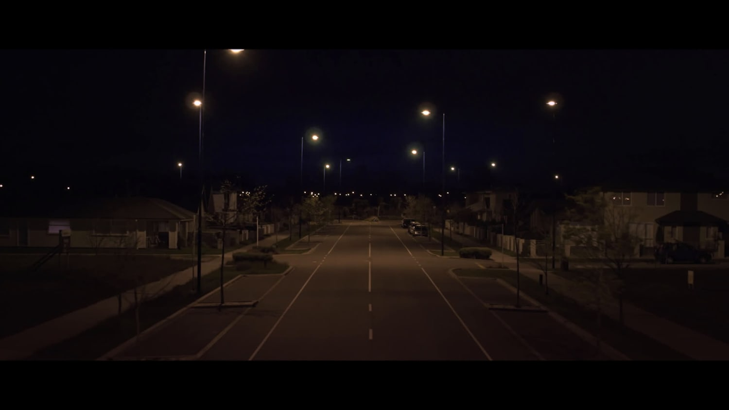 Night scene of a empty residential road with street lights on.