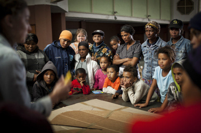 Farmworkers learning how to make solar cookers out of cardboard and chip packets after watching a Sunshine Cinema DIY Film
