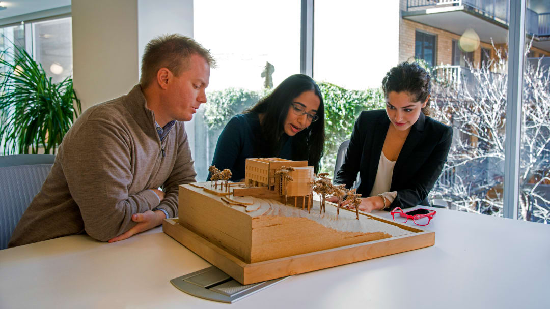 three people looking at building model