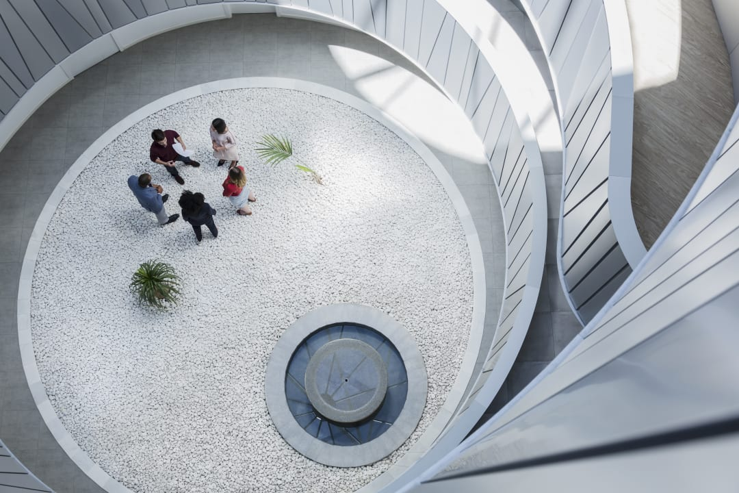 Coworkers talk in an atrium