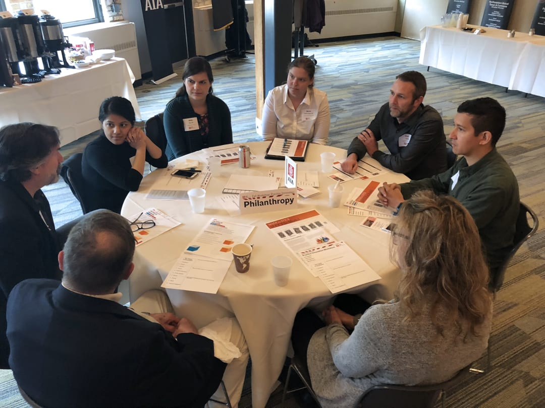 Group of eight professionals sitting at a round table discussing philanthropic opportunities for architecture firms