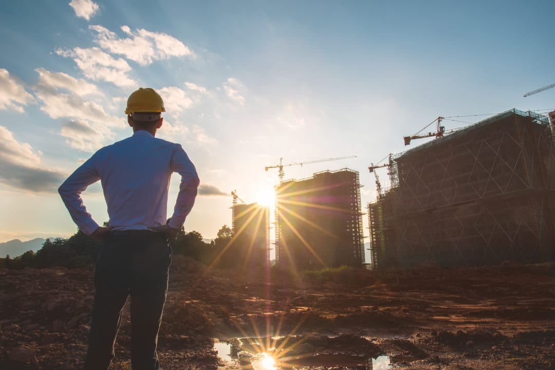 Architect gazing at construction site at sunset
