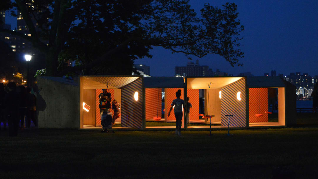 """Picture of the """"Salvage Swings"""" project lit up at night time, with a few people interacting with the project"""