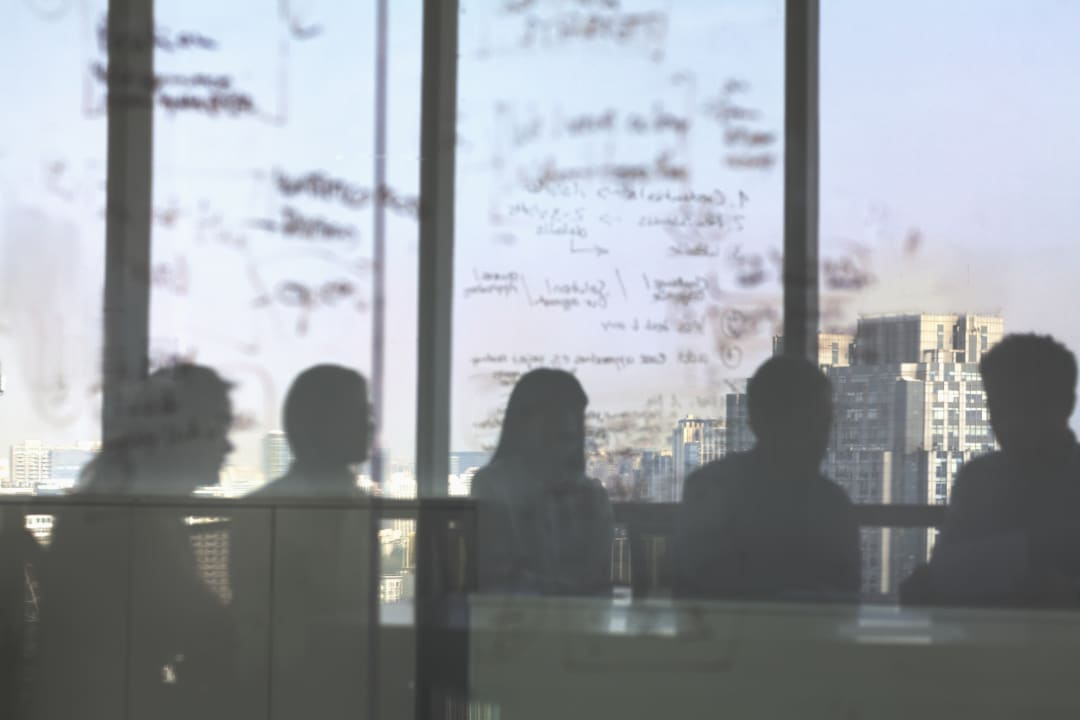 Individuals in office seen through clouded glass with writing on it
